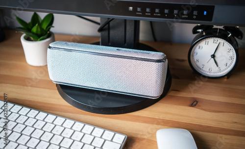 Fotografía  Wireless, gray loudspeaker lying on the desk next to the keyboard, computer mous