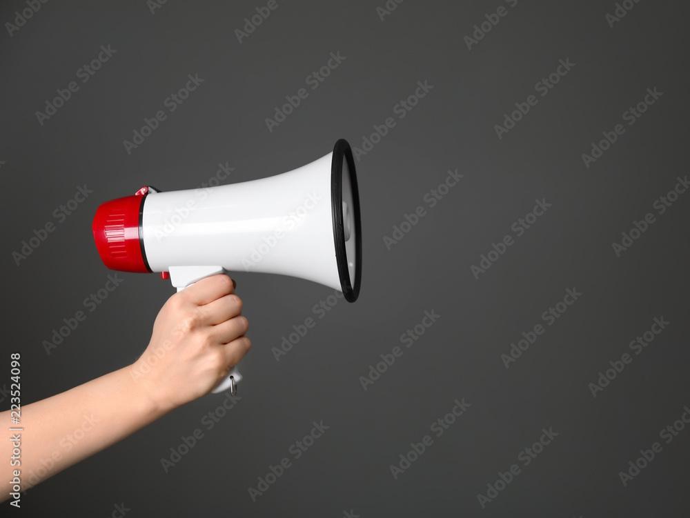 Fototapeta Woman holding megaphone on dark background