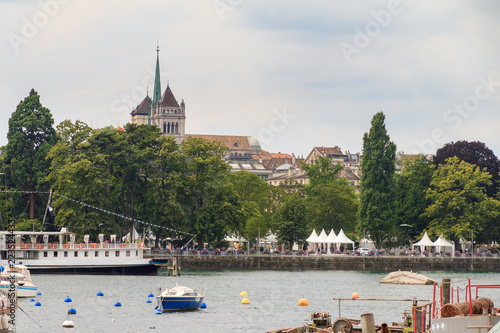 View of the skyline of Geneva, Switzerland, seen from a jetty in the lake with the St. Pierre Cathedral towering above the trees on a cloudy summer day