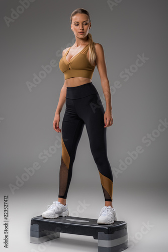 Fototapeta fit young woman doing step aerobics on grey obraz