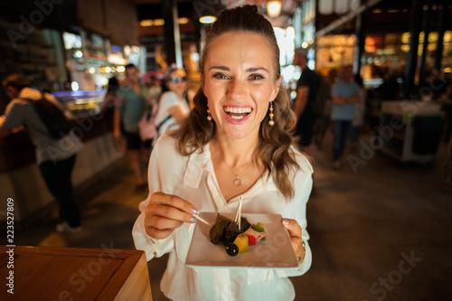 Naklejka premium szczęśliwa młoda kobieta na Mercado San Miguel próbująca lokalnych przysmaków