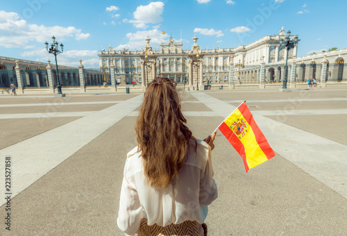 In de dag Madrid modern traveller woman with Spain flag against Royal Palace