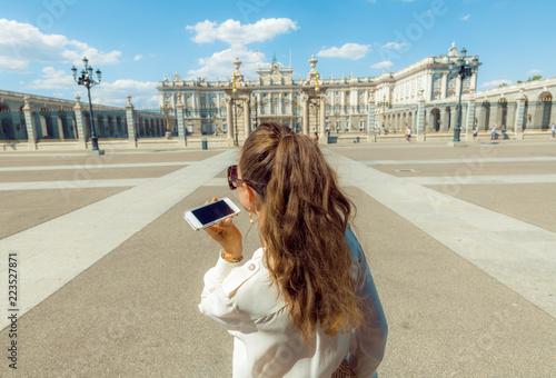 Naklejka premium nowoczesna kobieta podróżująca słuchając audioprzewodnika na smartfonie
