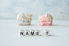 Concept Of Choosing Baby Name. Pink And Blue Decorative Straw Cradles With Thread Hearts And Text Name? On Light Background