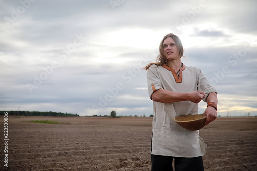 Fotografie, Obraz  A young peasant sows the field with grain