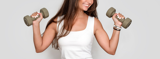 Attractive young fitness woman holding dumbells. Athletic girl doing a fitness workout with dumbbells on grey studio background.