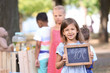 Little girl holding small blackboard with price near lemonade stand in park