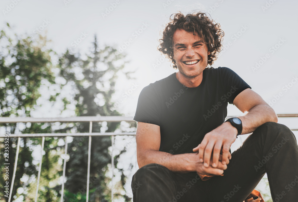 Fototapety, obrazy: Low view shot of happy stylish young man wears black t-shirt and wirstwatch on the street. Happy smiling man posing for advertisement with copy space, outdoor in the city street. People concept