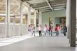 Primary school kids run holding hands in school corridor