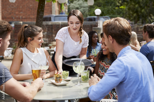 Fotografia, Obraz  Waitress Serving Drinks To Group Of Friends Sitting At Table In Pub Garden Enjoy