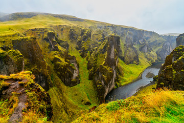 Fjaðrárgljúfur is a canyon in south east Iceland which is up to 100 m deep and about 2 kilometers long, with the Fjaðrá river flowing through it.