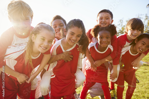 Obraz na plátne Kids in elementary school sports team piggybacking outdoors
