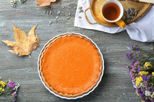 Baking Dish With Tasty Pumpkin Pie And Cup Of Tea On Wooden Table