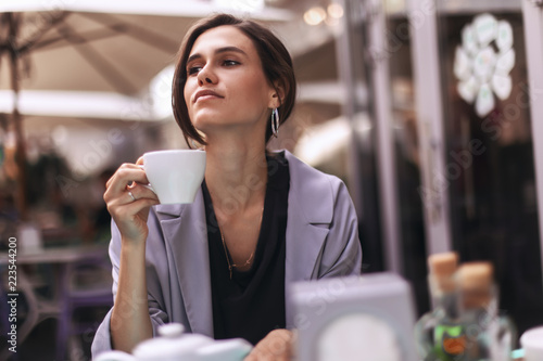 Attractive brunette bussines woman with tail drinking coffee or tea in restaurant. cofee break