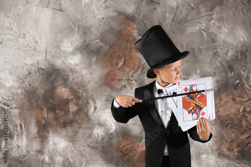 Photo Cute little magician showing trick with cards on grunge background