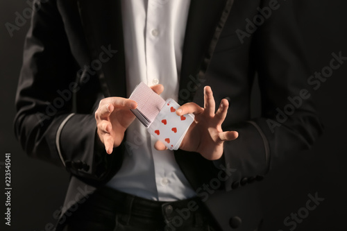 Magician showing tricks with cards on dark background, closeup Fototapeta