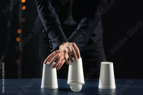 Magician showing tricks with cups on dark background Fototapete