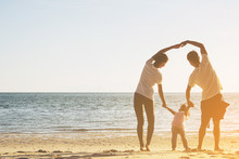 Selective Focus Happy Family With Little Girl Play At Sunset Beach.Happy Asian Family Outdoor Activity, Holding Hands Together Walking On Sand Seaside In Sunset During Vacations.