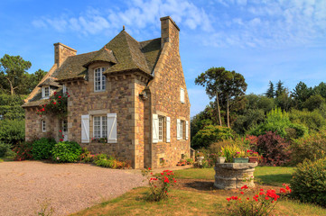 Beautiful view of a traditional French country house in Brittany, France, in summer with a blue sky