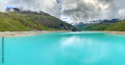 Beautiful 180 degree panoramic view of reservoir lake Moiry (lac de Moiry) with vibrant turquoise blue water at a low level in summer in Valais, Switzerland