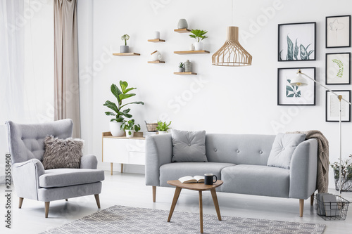 Grey armchair next to settee in bright living room interior with posters and wooden table Wallpaper Mural
