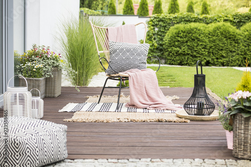 Fotografía Real photo of a white pillow and pink blanket on a rattan chair standing in the