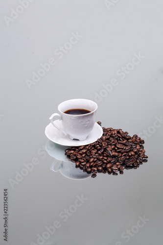 Foto op Plexiglas Cafe White cup with coffee. Coffee beans. Reflection in the mirror.
