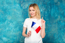 Happy Blond Woman Show Up With The Flag Of France On A Blue Wall Background. Learn French. European Woman.