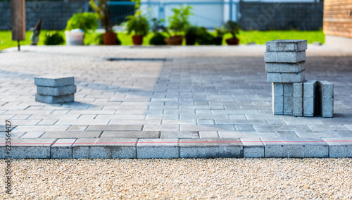 Laying gray concrete paving slabs in house courtyard driveway patio Fototapeta