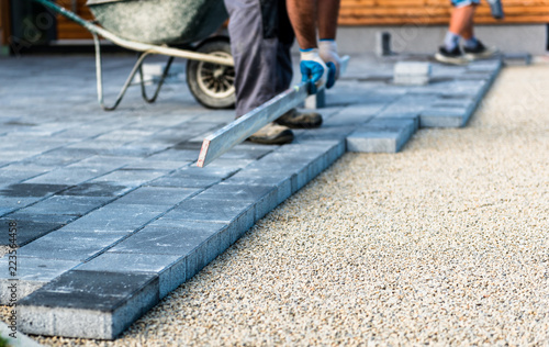 Fényképezés  Laying gray concrete paving slabs in house courtyard driveway patio