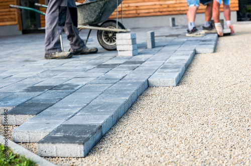 Fotografia, Obraz Laying gray concrete paving slabs in house courtyard driveway patio