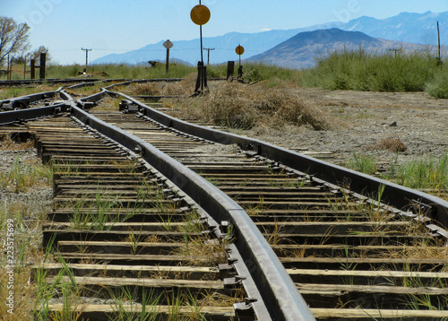 Fotografie, Obraz  Historic narrow gauge railroad tracks run toward a switch junction and signals in an old rail yard in Laws, California in the Owens Valley with the Sierra Nevada mountains in the distance