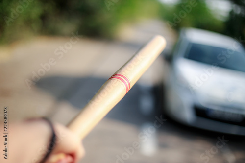 Photo Hand with baseball pointing to the car