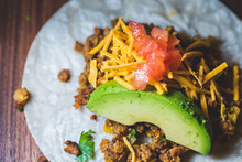A Close Up Of A Vegan Taco With Ground Meat, Avocado, Cheese, And Diced Tomato On A Wood Board.