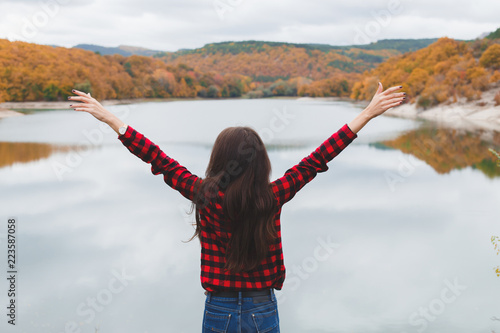 Fotografiet  Young woman wearing red plaid shirt standing alone near the lake in autumn