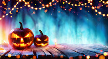 Halloween Party - Pumpkins And String Lights On Table In Dark Forest