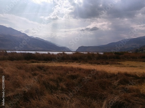 Yellow meadow with nearby lagoon, mountains at medium distance, sky with white clouds and black background, in the vicinity of the city of Cusco, Peru.