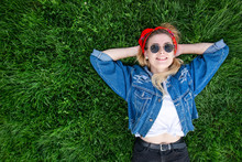 Happy, Stylish Girl In The Sunglasses And Denim Jacket Lying On The Lawn, Looking At The Camera And Smiling, Looking From Above. Copyspace
