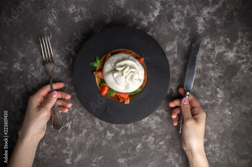 Woman eating burrata cheese on small wooden plate served with fresh tomatoes and basil on dark textured background