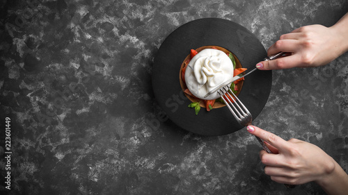 Deurstickers Buffel Woman eating burrata cheese on small wooden plate served with fresh tomatoes and basil on dark textured background