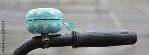 Photo  Drops of rain on a blue bike bell.
