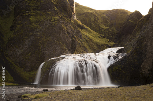 Poster Watervallen Idyllic view of waterfall falling from mountains