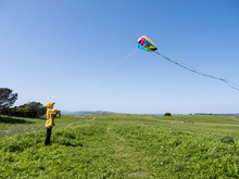Boy Flying Kite While Standing On Grassy Field Against Clear Blue Sky At Park