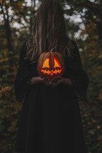 Spooky Woman Covering Face With Hair While Holding Illuminated Jack O' Lantern In Forest During Halloween