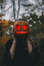 Woman Covering Her Face With Illuminated Jack O Lantern In Forest During Halloween