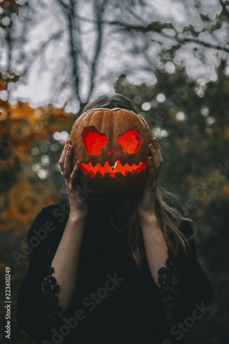 Young woman covering face with illuminated jack o' lantern in forest during Halloween