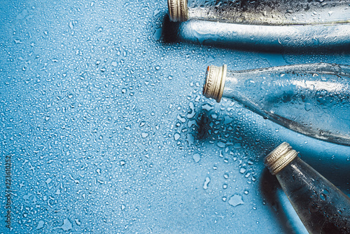 Carta da parati A glass bottle of water on blue background splashes drops of water on top