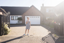 Girl Eating Ice Cream Cone While Standing Against House During Sunny Day