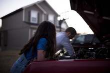 Daughter Looking At Father Repairing Car's Engine Against House During Sunset
