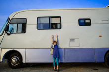 Portrait Of Girl With Arms Raised Standing By Motor Home